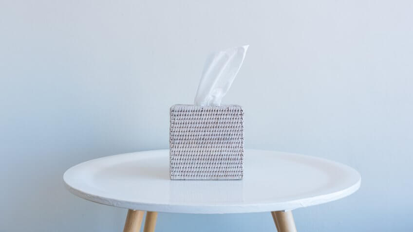 Close up of white tissue in rattan box on small table against neutral wall background - grief concept.
