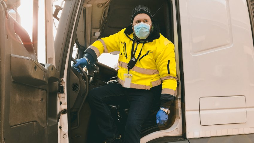 young transporter on the truck with face mask and protective gloves for Coronavirus.