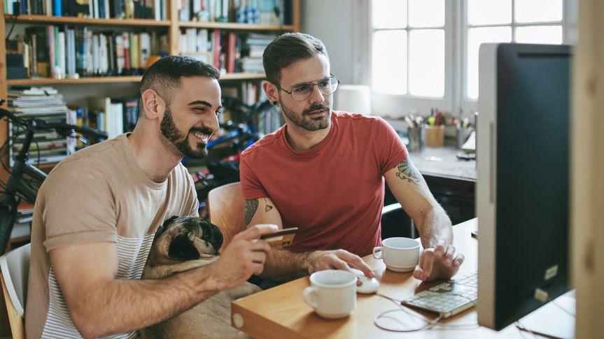Gay couple with pug shopping through computer at desk.