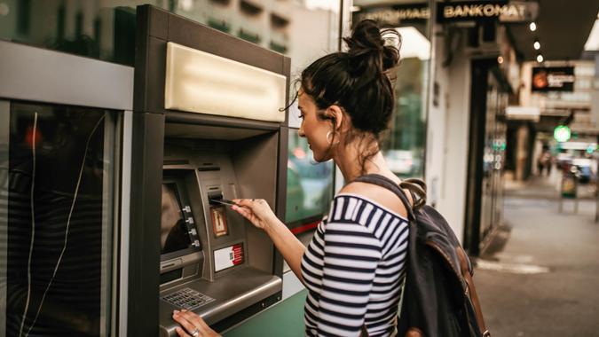 Woman using ATM machine.