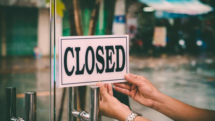 Hands of hairstylist closing barbershop.