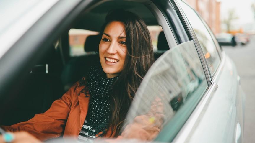 woman driving car smiling.