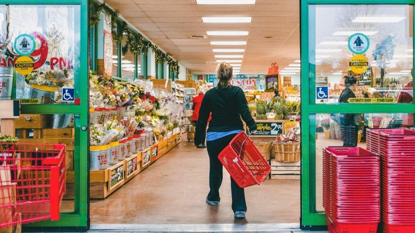 Reston, USA - December 18, 2017: Trader Joe's customer trolley shopping basket carrying carts by store entrance doors outside women, winter flower pots, gardening plants, pineapple in Virginia.