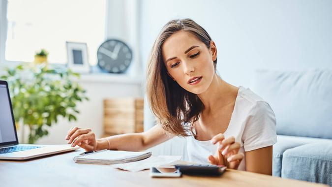 Young woman preparing home budget, using laptop and calculator.