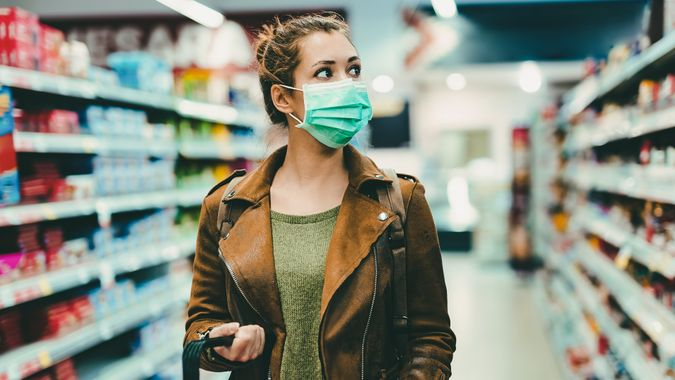 Young woman with face mask walking through grocery store during COVID-19 pandemic.