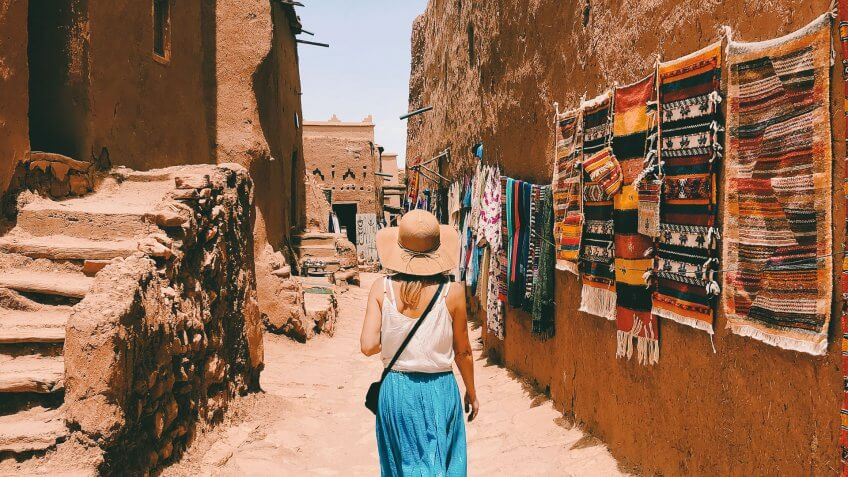 A young woman wearing a long blue skirt, white jersey and wicker hat is walking along a street in the Ait Ben Haddou village, hung with traditional Moroccan carpets.
