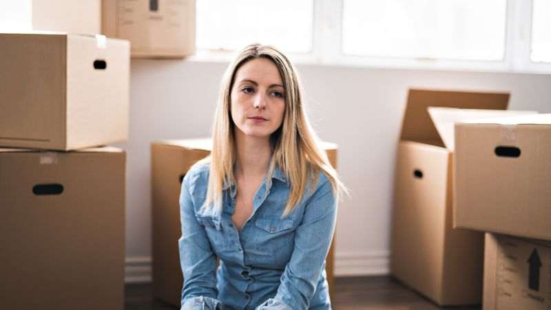A very sad woman with box at home.