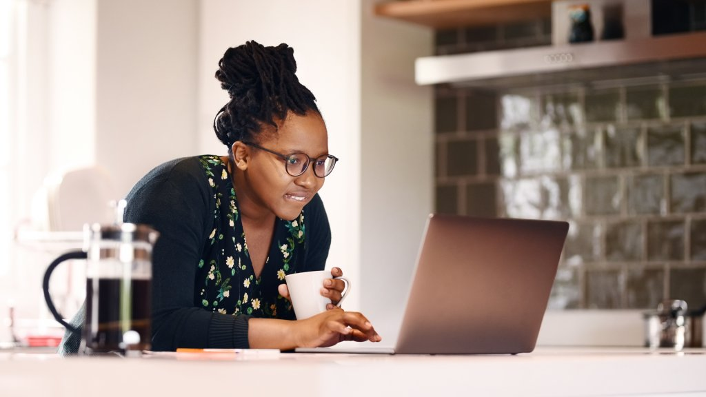 Shot of a young african american woman with a coffee cup using laptop in kitchen at home.