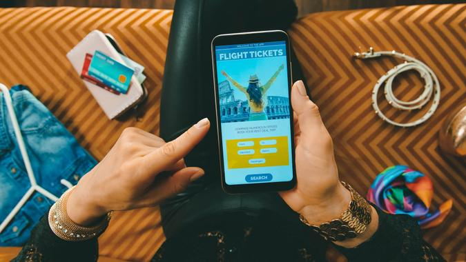 elegant housewife sitting on sofa in the modern living room booking airplane tickets online on a smartphone.