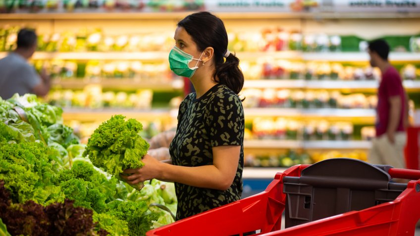 Alarmed female wears medical mask against coronavirus while grocery shopping in supermarket or store- health, safety and pandemic concept - young woman wearing protective medical mask for protection from virus covid-19 and stockpiling food.