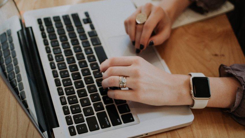 woman typing password on laptop