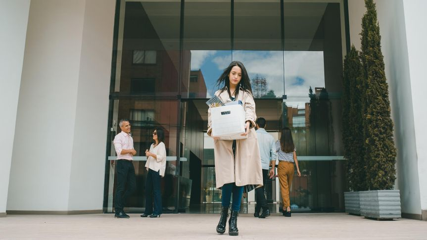 Fired woman leaving the office building with her belongings in a box and looking sad - losing a job concepts.