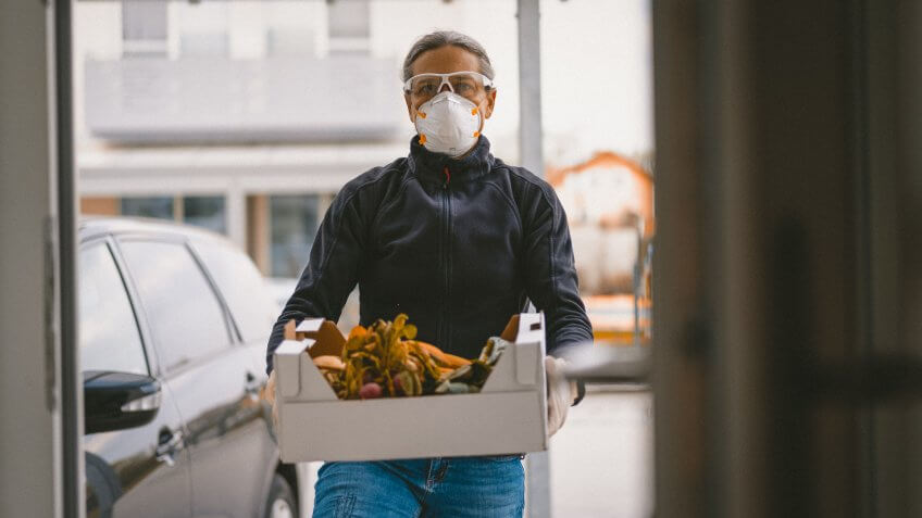 woman with covid-19 mask with groceries