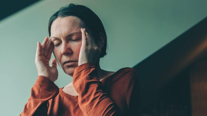 Woman with severe migraine headache, selective focus.