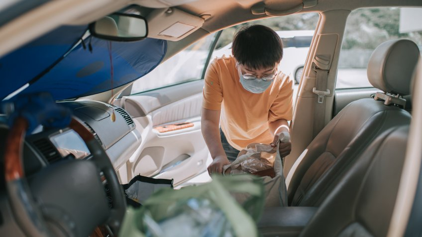 an asian chinese mid age woman removing reusable bags from her car which she just bought all groceries from supermarket with her face mask.