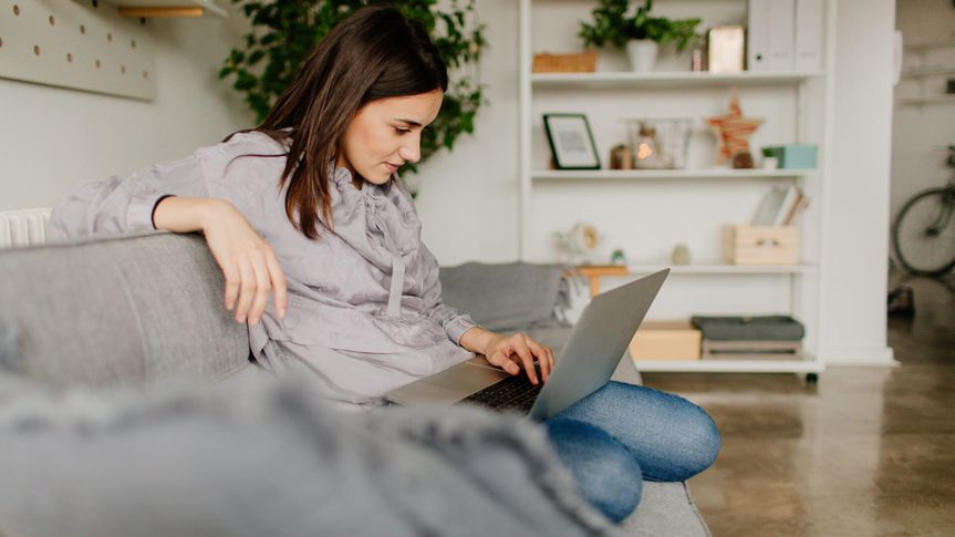 Young woman using computer at home.