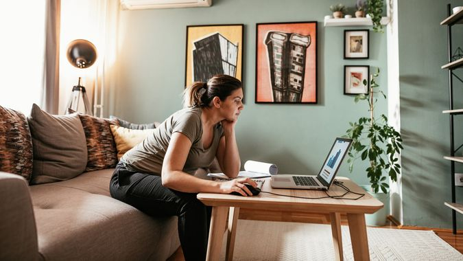 Woman working from home due to restrictive measures, lockdown and quarantine due to pandemic Coronavirus.