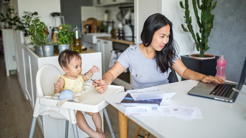 Young Asian mother working and spending time with baby at home.