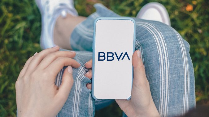 Mockup of female hand holding cell phone with blank white screen against grass background.