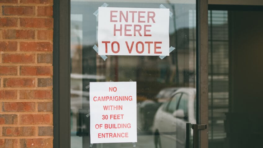 Enter Here to Vote sign on a polling location in the United States primary election on Super Tuesday.
