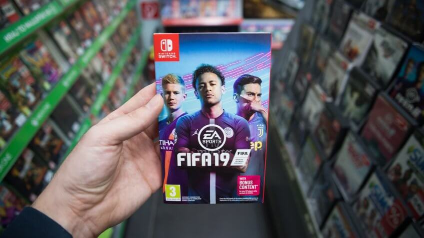 Bratislava, Slovakia, march 8, 2019: Man holding Fifa 19 videogame on Nintendo Switch console in store.