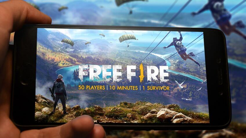Kyiv, Ukraine; May 11, 2019: Hand holding phone with Free fire logo displayed in it with fluctuating graphic on background.