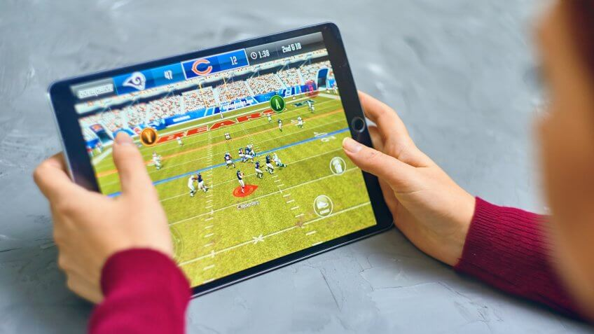 Bishkek, Kyrgyzstan - January 21, 2019: Girl playing a mobile game madden nfl of ea sports company on ipad pro.