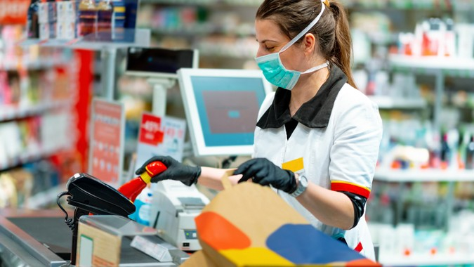 Woman cashier wearing protective face mask and gloves to prevent viruses, scanning disinfection products at the cash register and packing in paper bag.