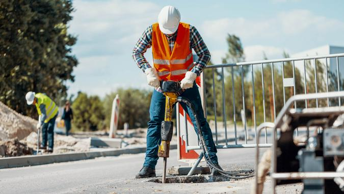 Worker in reflective vest with drill repairing street during roadworks.
