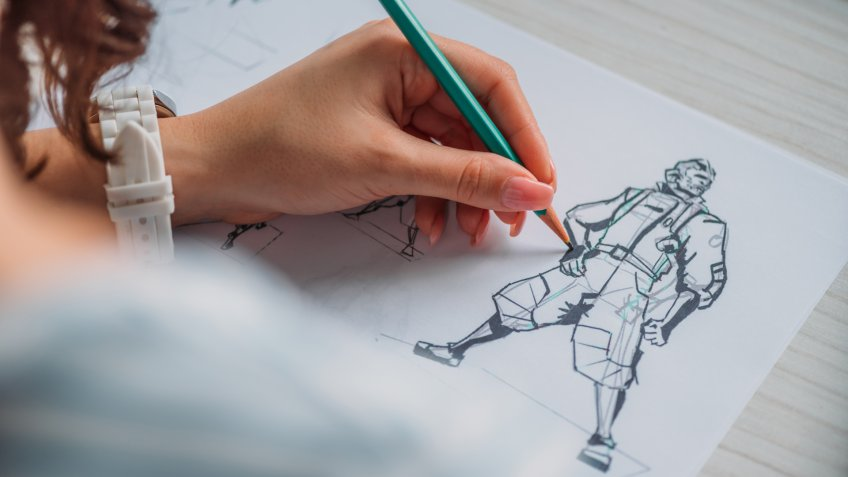 selective focus of illustrator drawing cartoon character on paper.