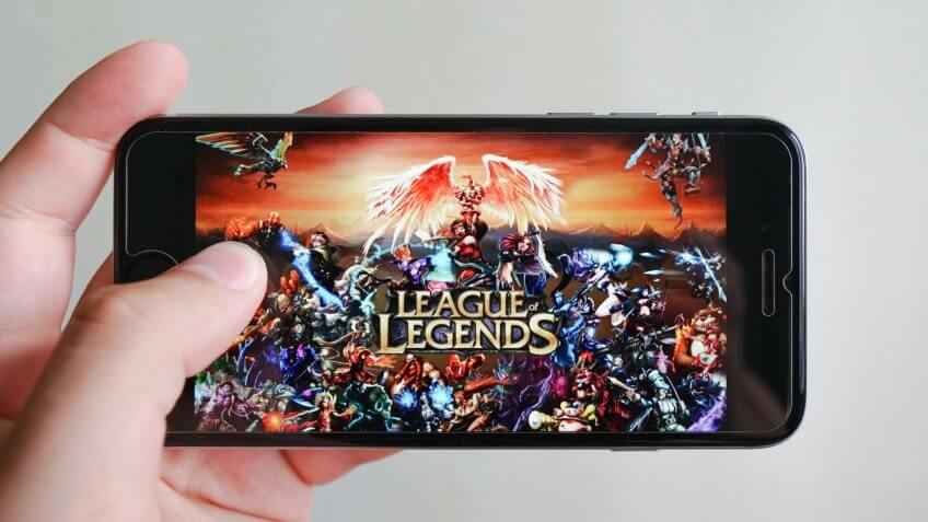 Los Angeles, California, USA - 9 June 2019: Hands holding a smartphone with League of Legends game on display screen, Illustrative Editorial.