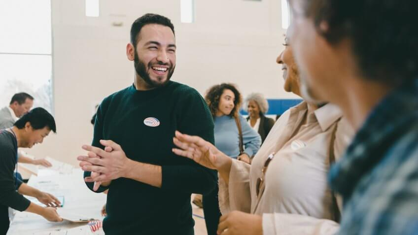 Cheerful mid adult Hispanic man smiles and laughs with friends as they wait to vote on election day.