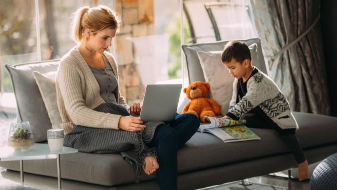 Woman working on laptop with her son reading a storybook.