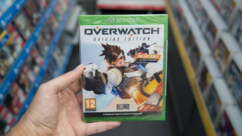 Bratislava, Slovakia, circa april 2017: Man holding Overwatch videogame on Microsoft XBOX One console in store.