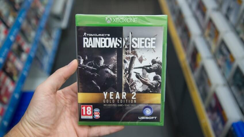 Bratislava, Slovakia, circa april 2017: Man holding Tom Clancy's Rainbow Six: Siege Gold Edition Year 2 videogame on Microsoft XBOX One console in store.