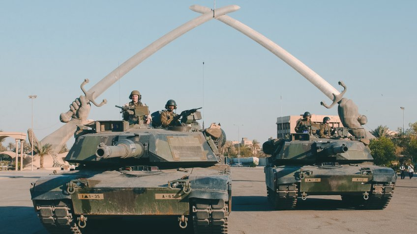 """US Army (USA) M1A1 Abrams MBT (Main Battle Tank), and personnel from A Company (CO), Task Force 1st Battalion, 35th Armor Regiment (1-35 Armor), 2nd Brigade Combat Team (BCT), 1st Armored Division (AD), pose for a photo under the """"Hands of Victory"""" in Ceremony Square, Baghdad, Iraq during Operation IRAQI FREEDOM."""