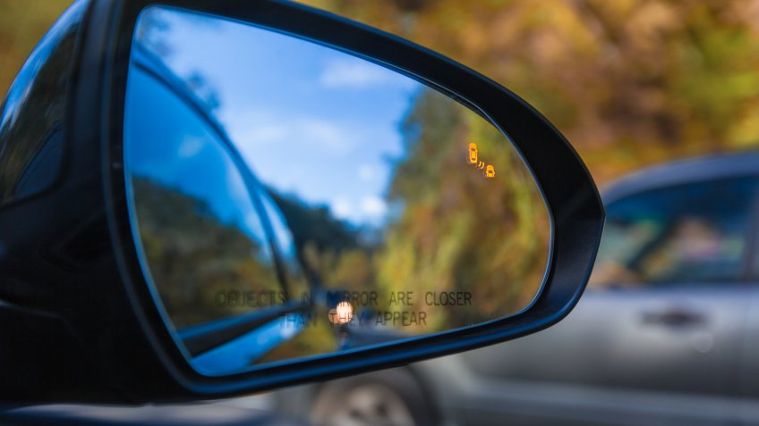 Objects in mirror are closer than they appear on car with Blind Spot Assist Warning LED Sensor Light.