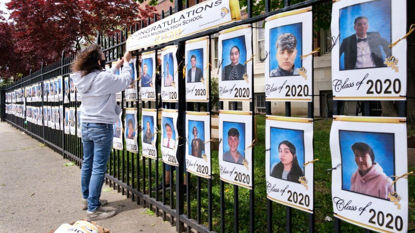 Mandatory Credit: Photo by JUSTIN LANE/EPA-EFE/Shutterstock (10652014d)School employee Luz Carlson hangs a sign over pictures of the graduating senior class displayed on the fence at James Madison High School in Brooklyn, New York, USA, 19 May 2020.