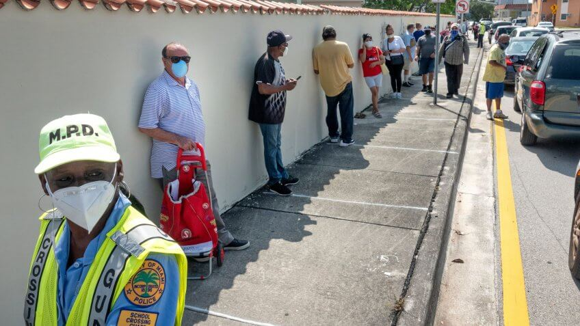 Mandatory Credit: Photo by CRISTOBAL HERRERA/EPA-EFE/Shutterstock (10652015a)A Miami Police officer guards the line of the people who are going to receive bags of hot food, cooked in local restaurants, in Little Havana, Miami, Florida, USA, 19 May 2020.
