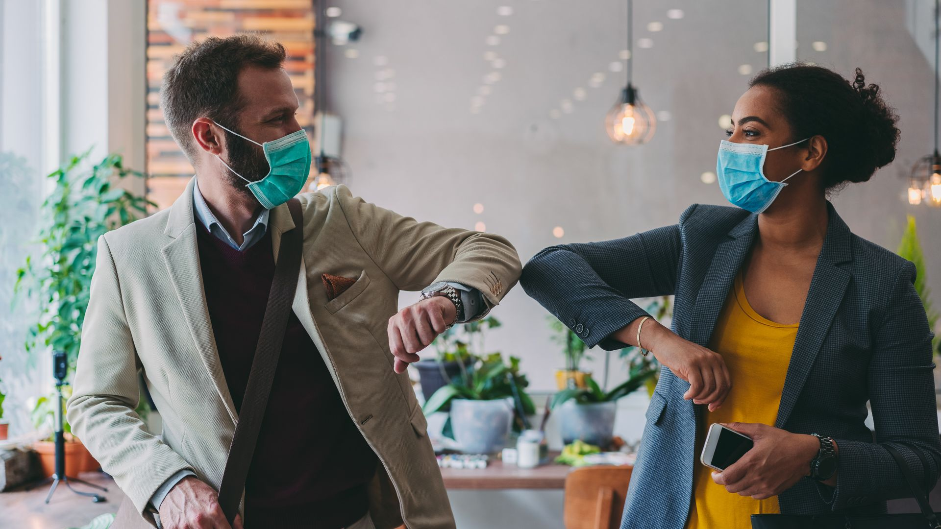 Colleagues in the office practicing alternative greeting to avoid handshakes during COVID-19 pandemic.