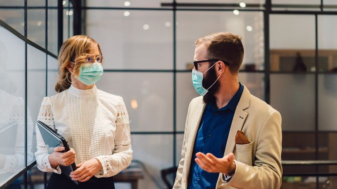 Businesspeople wearing masks in the office for safety during epidemic situation.