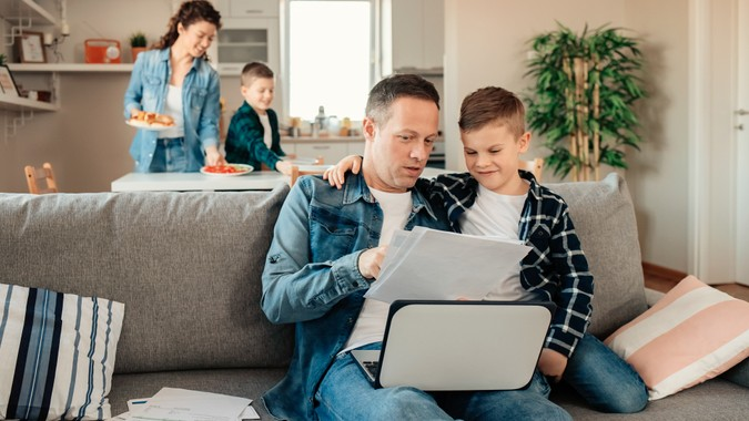 Father Works From Home While His Younger Son Makes Him Company While Mum With Other Son Sets Lunch in the Background.