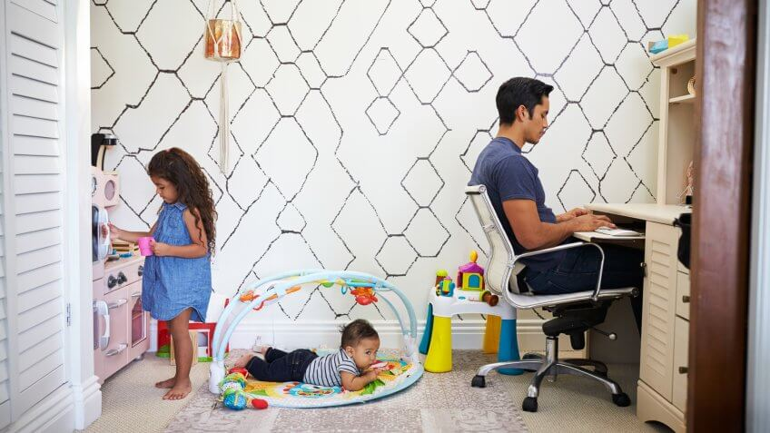 Dad sits working at a desk at home while his baby son and young daughter play in the room behind him.