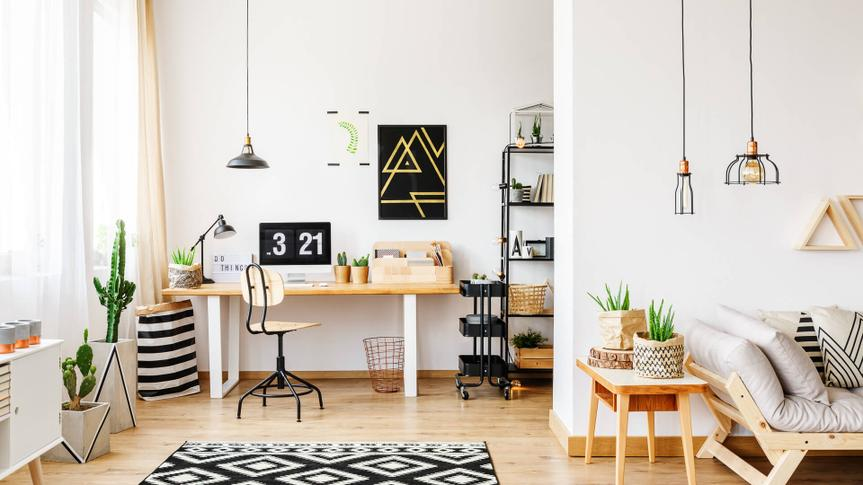 Black and white geometric carpet in multifuncional workspace with painting on wall above desk.