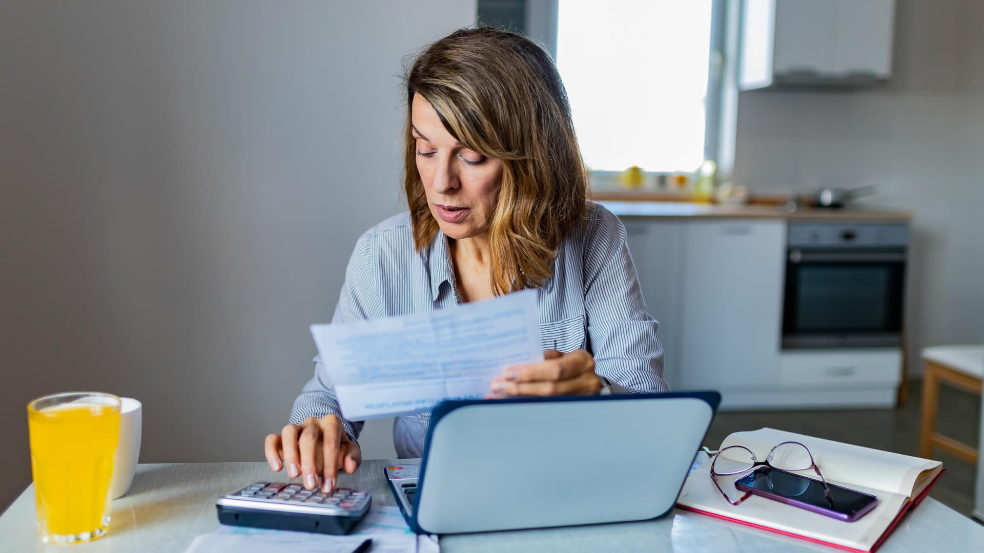 Senior Woman Calculating Domestic Expenses Making Notes, Surrounded With Papers and Gadgets, Sitting at Dining Table.