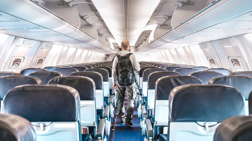 Inside view of commercial airplane with lonely man traveler - Emergency travel concept about flight cancellation - Aerospace industry crisis with empty plane on bright azure filter.