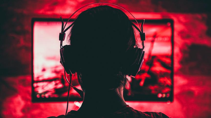 Woman wearing headphones playing video games late at night.