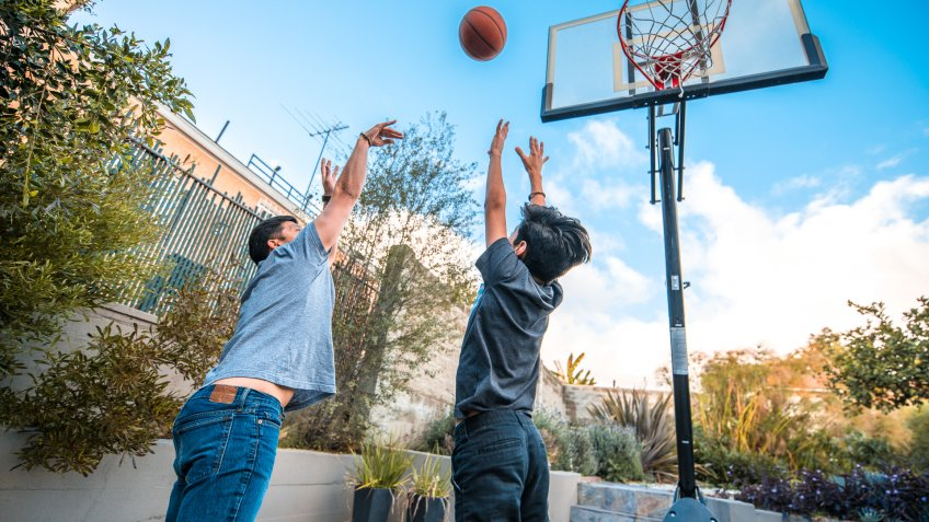 Father and son with arms raised playing basketball.
