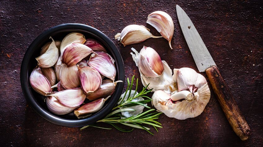 Vegetables: Garlic cloves in a black bowl shot from above on rustic brown background.