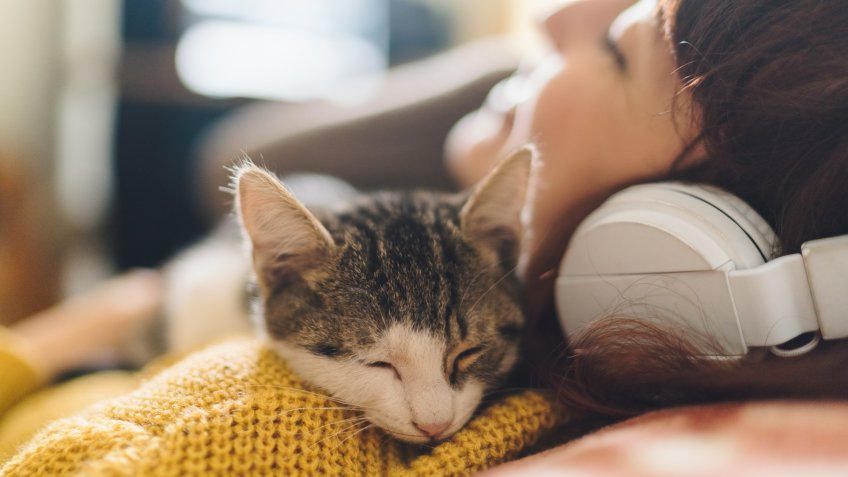 Gen Z girl with eyes closed hugging a cat and enjoying music.